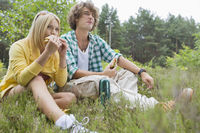 Young hiking couple eating sandwiches while relaxing in field