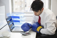 Young indian businessman wearing boxing gloves while using calculator at office desk