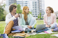 Young man having coffee while studying with female friends at college campus