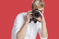 Young man taking picture with digital camera over red background
