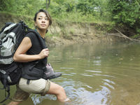 Young woman carrying backpack walking in water looking over shoulder