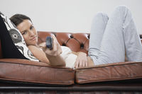 Young woman holding remote control lying on sofa