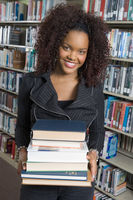 Young woman in a library holding stack of books
