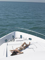 Young woman in bikini sunbathing on yacht elevated view