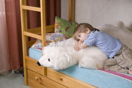 Toy : 5 year old boy lies on bunk bed with polar bear soft toy