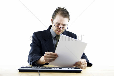 Determined : A bespectacled man in business suit sitting at his desk reading some notes
