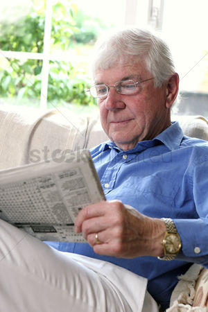 Bespectacled : A bespectacled old man sitting on the couch reading newspaper