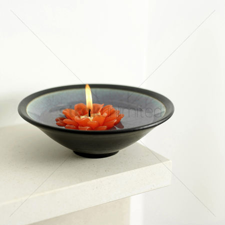 Refreshment : A bowl of water with lit candle floating on it