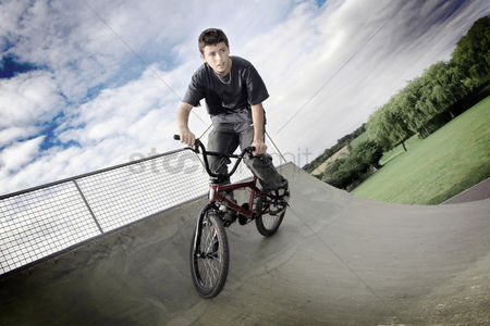 Trees : A boy cycling in a skateboard park