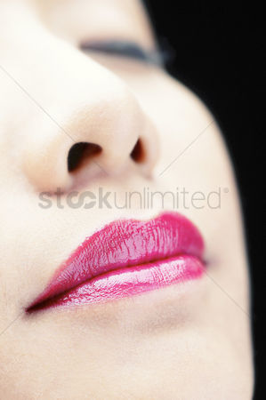 Attraction : A close-up picture of a lady in bright pink lipstick closing her eyes