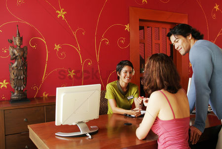Choosing : A couple choosing a spa package at the reception counter of thai resort spa