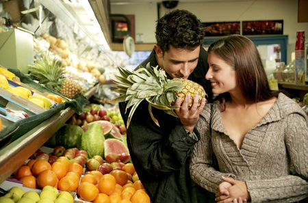 Supermarket : A couple sniffing a pineapple