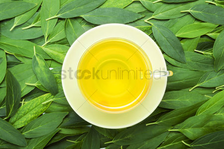 Food  beverage : A cup of tea with fresh tea leaves on the background