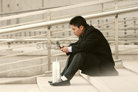 Stairs : A guy in business suit sitting on the stairs text messaging