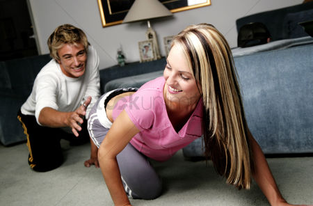 Closeness : A lady crawling away while her boyfriend crawl-chasing from behind
