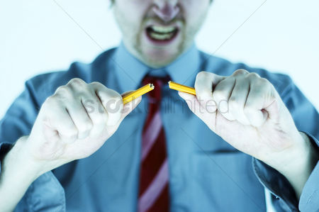 Blow up : A man in blue shirt and tie breaking a pencil into two