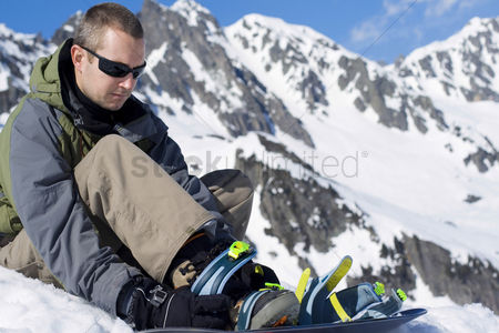 Coldness : A man preparing himself for snowboarding