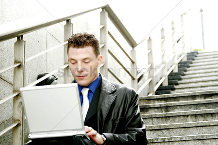 Stairs : A man sitting on the stairs using his laptop