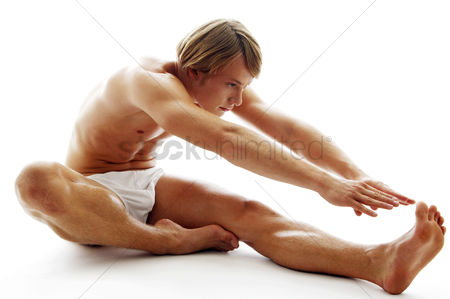Strong : A shirtless man in white underwear stretching his hands to touch his feet