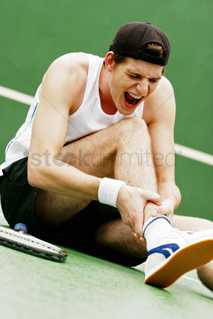 Pain : A tennis player screaming in pain after he sprained his leg
