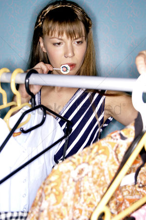 Selection : A woman eating lollipop while choosing her clothes