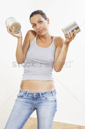 Selection : A woman in jeans holding up two tins of paint