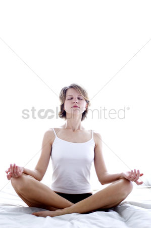 Practising yoga : A woman in white camisole meditating on the bed