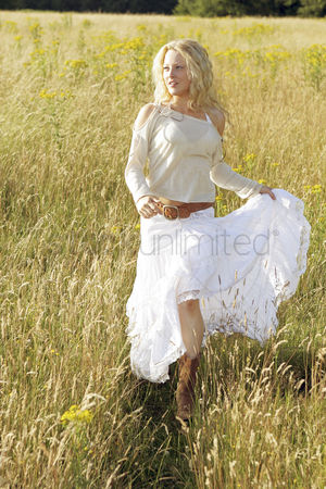 Having fun : A woman running happily on the prairie