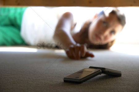 Cellular phone : A woman trying to get a hand phone from under the bed