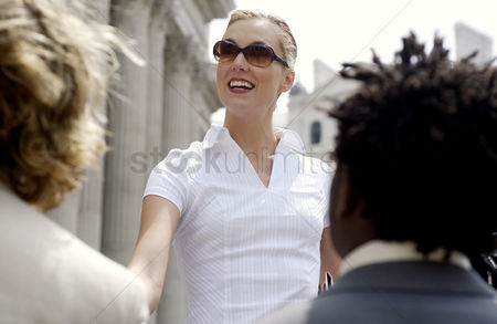 Business suit : A woman with sunglass shaking hands with a man while another man watching