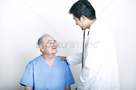Examination : A young asian doctor comforting a senior adult patient