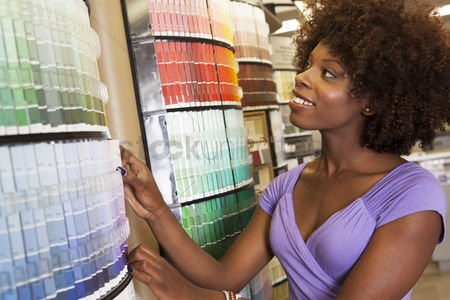 Supermarket : African american woman looking at paint swatches at hardware store
