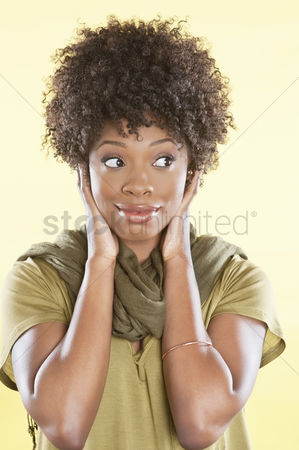 Curly hair : African american woman looking sideways over colored background