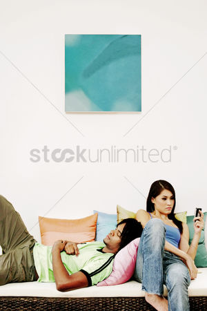 Sitting on lap : An african american man laying on the couch sleeping while his girlfriend is text messaging