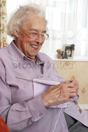 Bespectacled : An old bespectacled lady sitting on the couch knitting