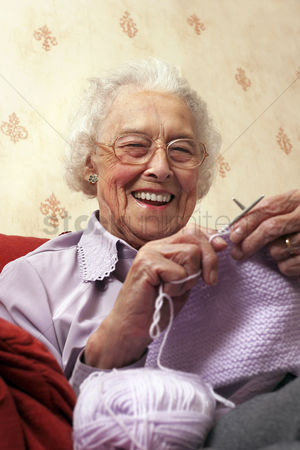 Lady : An old bespectacled lady sitting on the couch knitting