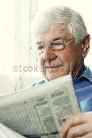 Bespectacled : An old bespectacled man reading newspaper