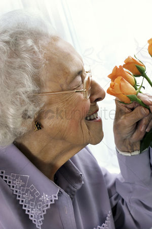 Lively : An old bespectacled woman sniffing flowers
