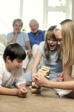 Careful : An old couple sitting on the couch watching their grandchildren playing building blocks on the floor