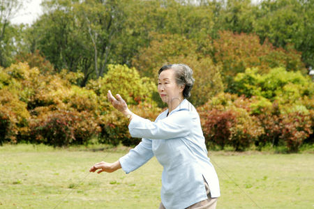 Grass : An old woman practicing tai chi in the park