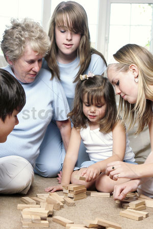 Children playing : An old woman sitting on the floor playing building blocks with her grandchildren