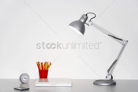 Desk : Angle poise lamp laptop clock pencils and pda on desk
