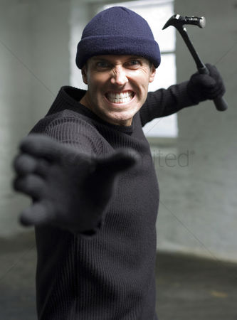 Forbidden : Angry burglar attacking with a hammer