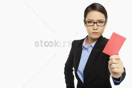 Frowning : Angry businesswoman holding up  a red card