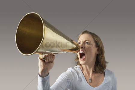 Head shot : Angry mid-adult woman shouting through megaphone