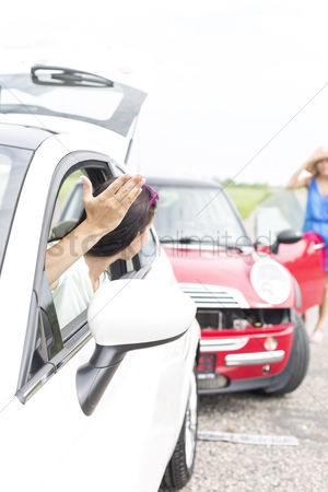 On the road : Angry woman gesturing while talking to female crashing car on road