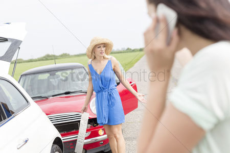 On the road : Angry woman standing by damaged cars with female using cell phone in foreground