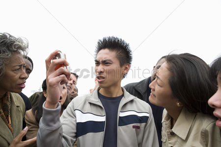 Demonstration : Angry young man holding mobile phone in crowd