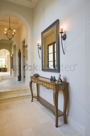 Steps : Antique console table with grey framed mirror in hallway