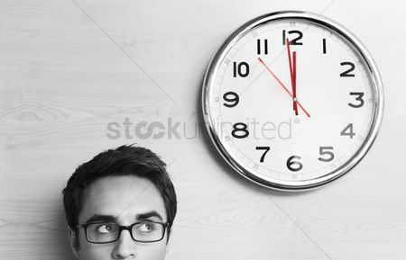 Alone : Anxious businessman looking at office clock